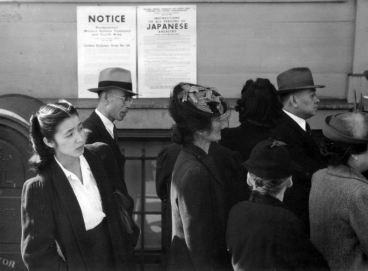 Japanese Americans in front of poster with internment orders