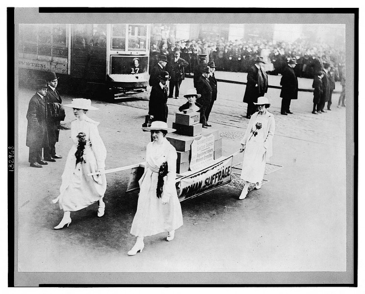 Photograph shows four women carrying ballot boxes on a stretcher during a suffrage parade in New York City, New York.