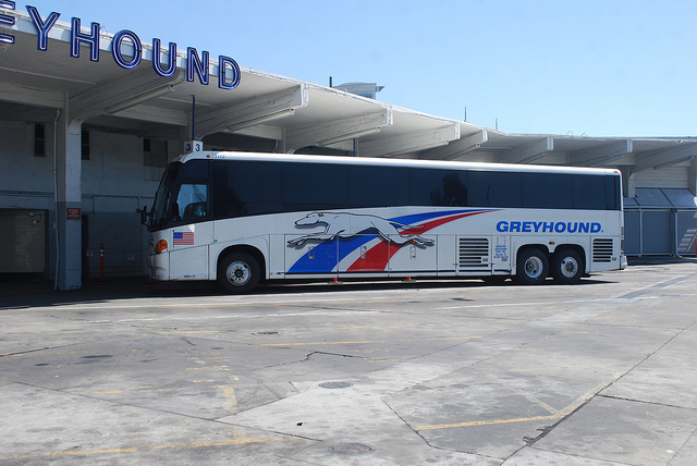 Greyhound lines # 7170, a MCI G4500, waits for passengers in back of the Oakland, CA Greyhound terminal. Taken by a Nikon D40x with a Nikon 18-55mm non-VR kit lens. (at 26). Photo by Paul Sullivan. Creative Commons License via Paul Sullivan Flickr.