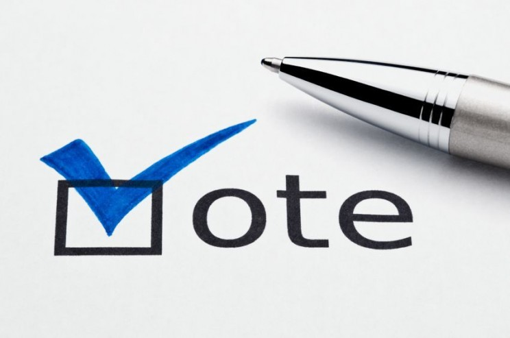 Blue checkmark on vote checkbox, pen lying on ballot paper
