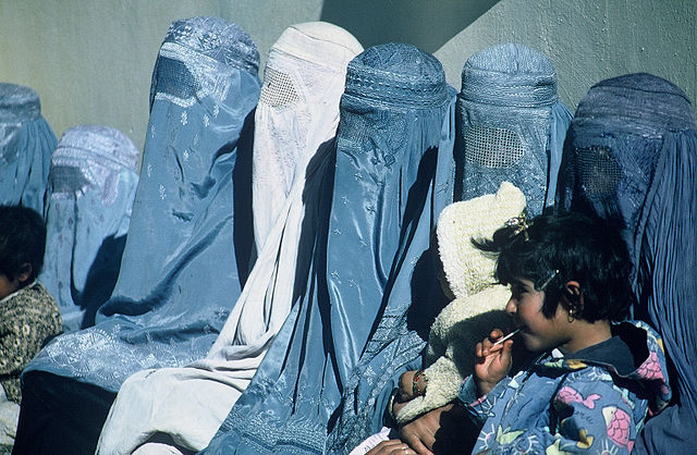 A Group of Women Wearing Burkas. Afghanistan women wait outside a USAID-supported health care clinic. Photo by Nitin Madhav (USAID). Public domain via Wikimedia Commons.