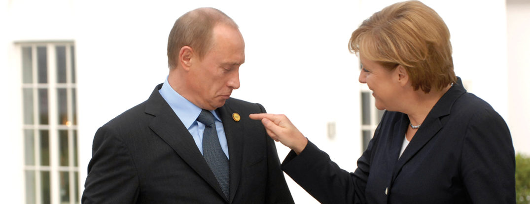German Chancellor Angela Merkel points to a badge on Russian President Vladimir Putin's lapel in Heiligendamm, G8 Summit 2007. Photo REGIERUNGonline / Kühler via The Press and Information Office of the Federal Government of Germany.